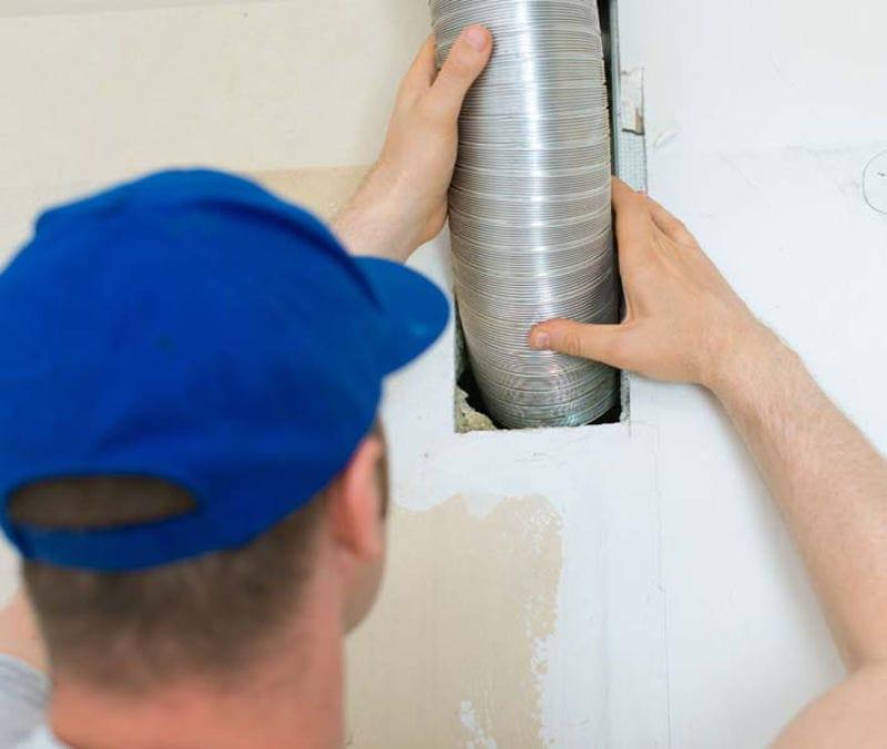 Man setting up ventilation system indoors.